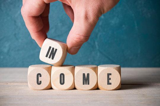 """hand stapelt würfel mit dem Wort """"income"""""""