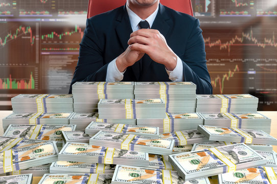 businessman sitting with pile of 100 dollar banknote