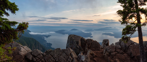 Beautiful Panoramic View of Canadian Mountain Landscape covered in clouds during a vibrant summer sunset. Taken on top of St Mark's Summit, West Vancouver, British Columbia, Canada. Fototapete