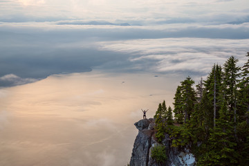Wall Mural - Female Hiker on top of a mountain covered in clouds during a vibrant summer sunset. Taken on top of St Mark's Summit, West Vancouver, British Columbia, Canada.