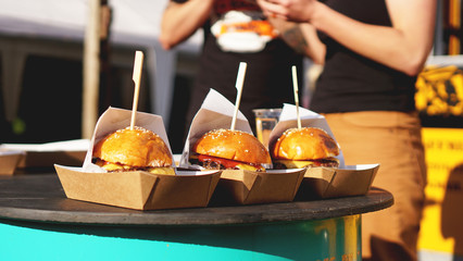Beef burgers being served on food stall on open kitchen international food festival event of street food
