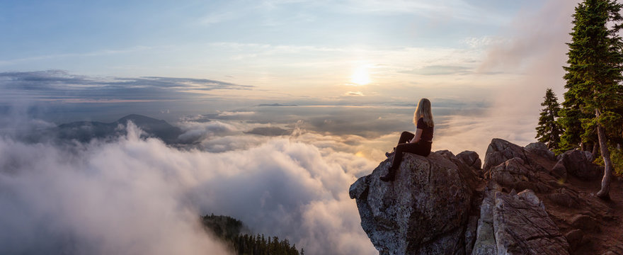 Adventurous Female Hiker on top of a mountain covered in clouds during a vibrant summer sunset. Taken on top of St Mark's Summit, West Vancouver, British Columbia, Canada.