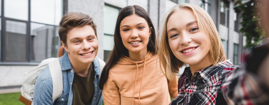 panoramic shot of happy teenagers taking selfie and smiling