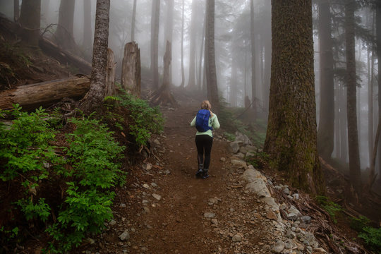Adventurous girl hiking on a trail in the woods during a foggy and rainy day. Taken in Cypress Provincial Park, Vancouver, British Columbia, Canada.