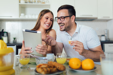 Happy couple enjoying breakfast time together at home and using digital tablet.