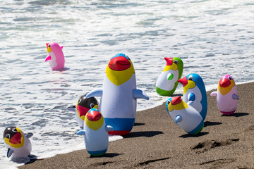 Beach toy background. Selective focus on a group of eight colorful inflatable rubber penguin toys at a sandy sunny beach. Space for advertising. Macro.