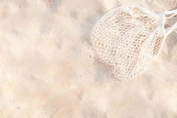 Top view of sandy beach with beach mesh bag Background with copy space. Wall mural