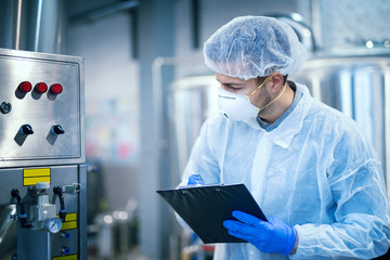 Technologist expert in protective uniform with hairnet and mask taking parameters from industrial machine in food production plant. Wall mural