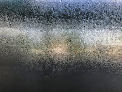 Transparent glass in the mist from the humidity in the air in cool tones on the background blurred. Surface of blue condensation, morning at Phuket International Airport