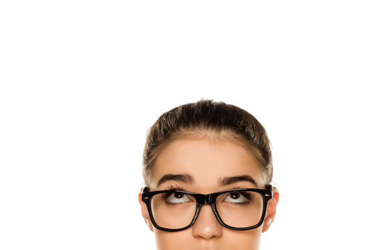 Young confused woman with glasses looking up on white background