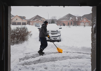 Man and child shovelling snow off of a driveway on a snowy day.