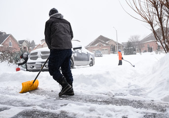 Man and children shovelling snow off of a driveway on a snowy day.