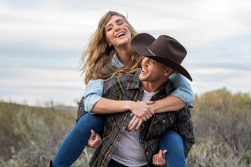 Western wear young couple giving piggy back ride and laughing