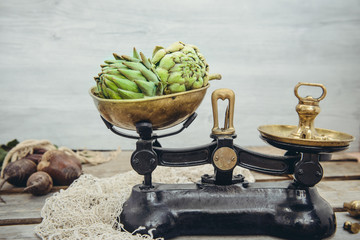 Green delicious artichoke vegetables on the vintage weights, standing on the rustic wooden background. Farmer local market counter, Kitchen table. Copy space.