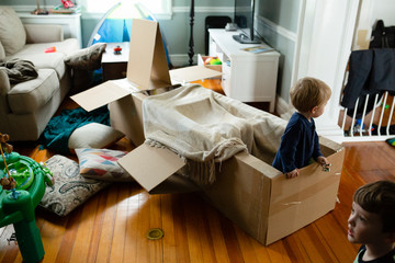 Kids engage in pretend play indoors with spacecraft made of cardboard