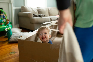 Happy toddler boy looks up at brother smiling inside cardboard toy