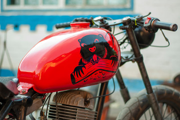 Old renovated red-colored motorcycle with a beaver stick on a tank.
