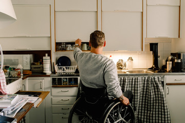 Rear view of disabled man opening cabinet in kitchen at home