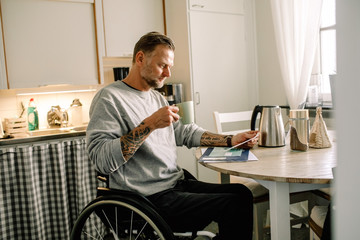 Bearded man in wheelchair reading mail at home