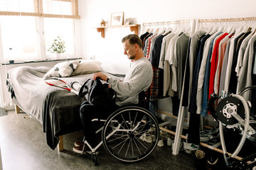 Man in wheelchair packing bag at home