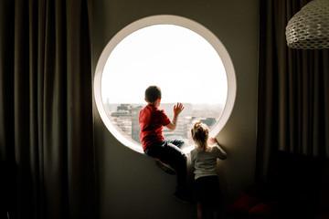 Rear view of siblings looking through window