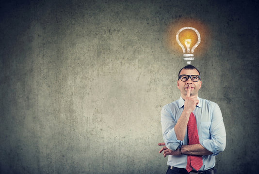 thinking business man looking up at bright light bulb above head