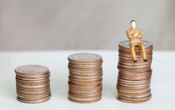 Figure miniature businessman or small people sit on money coin and book background for money and financial business shopping concept.