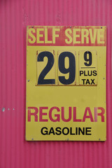 An old weathered sign at a defunct gas station showing the price for regular of decades ago
