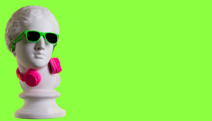 Statue. Earphone. Isolated. Gypsum statue of Aphrodite's head. Creative. Plaster statue of Aphrodite's head in green sunglasses. On a green background.