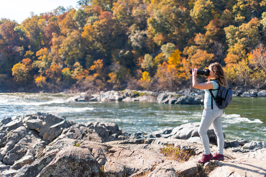 Young woman photographer taking photo picture with camera of view of Potomac river in Great Falls with autumn colorful foliage in Maryland