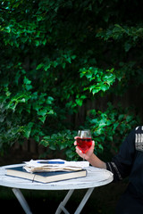 Woman holding wine glass while sitting at table outdoors