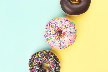 Three tasty doughnuts on turquoise background. Wall mural