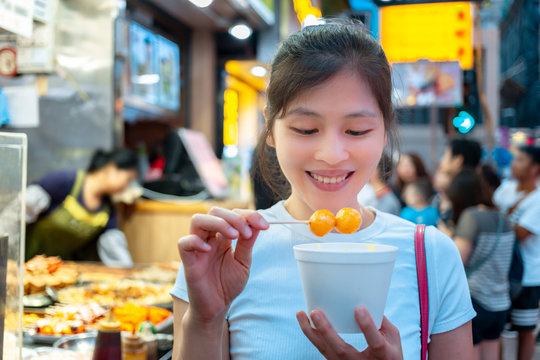 Asian young female eating famous street food - fish ball, in Hong Kong