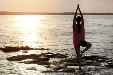 Young woman practicing yoga near river in morning