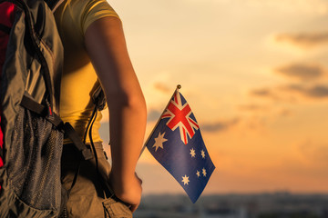 woman hiker on the top of mountain in shorts and a t-shirt with a backpack and flag of Australia on a sunset sky background