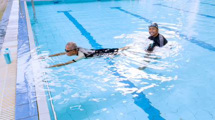 Elderly man learning swims with his son