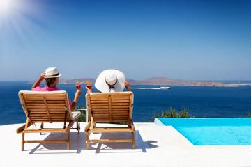 Attraktives Paar auf Reisen entspannt bei einem Aperitif am Pool auf Liegestühlen und genießt den Ausblick auf das Meer Wall mural