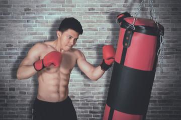 Shirtless young man hits on a boxing bag