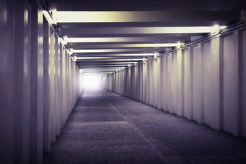 An image of light at the end of a underground concrete tunnel. A long concrete tunnel with lanterns in the city underground. Underpass Wall mural