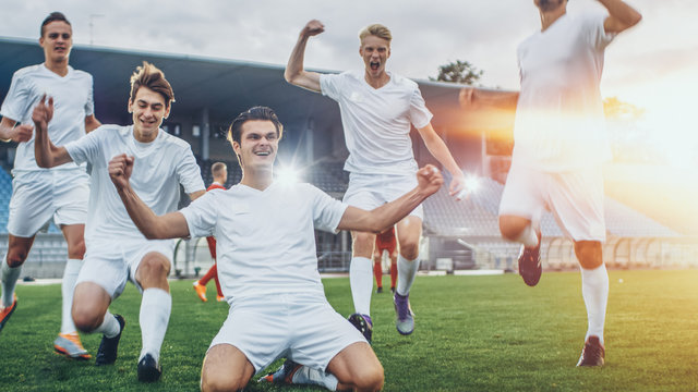 Captain of the Soccer Team Stands on His Knees Celebrates Awesome Victory, Makes YES Gesture Champion Team Joins Him. Successful Happy Football Players Celebrate Victory. Shot with Warm Sunlight Flare