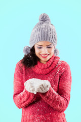 Smiling woman holding snow on her palms