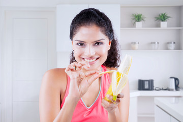 Smiling woman peels banana in the kitchen