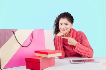 Smiling woman pointing shopping bags on studio