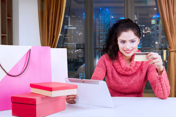 Smiling woman using a credit card and tablet