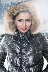 Smiling woman wears winter jacket in snowy park