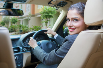 Smiling young businesswoman driving a car
