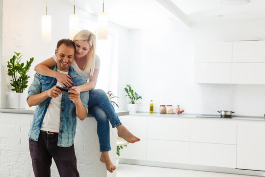 couple, woman and man using smartphone at kitchen. Ultra wide home shot.