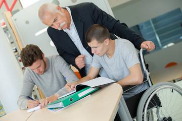 teacher helping student in wheelchair