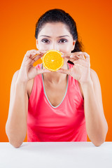 Woman covering her mouth with orange fruit