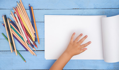 children's hands draw with pencils in the album on the blue table